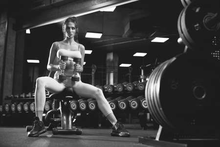 From below view of female bodybuilder training with dumbbells. Portrait of brunette fitnesswoman with fit body looking at camera, sitting on bench in gym, black and white. Concept of bodybuilding. Stockfoto