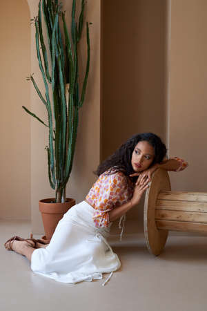 Gorgeous mulatto girl with curly hair posing near tall succulent plant in flower pot, sitting on floor and leaning on wooden wheel. Stunning half african woman wearing blouse, white skirt and heels. Standard-Bild
