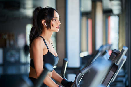 Side view of brunette woman in black sportswear and wireless headphones doing hard cardio workout on orbitrek. Sexy muscular female with slim body running in empty gym. Concept of sport, bodybuilding.
