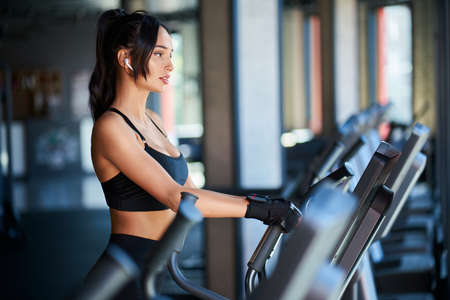 Side view of brunette woman in black sportswear and wireless headphones doing hard cardio workout on orbitrek. Sexy muscular female in gloves, with slim body running in empty gym. Concept of sport.