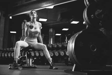 From below view of female bodybuilder training with dumbbells. Portrait of brunette fitnesswoman with fit body looking away, sitting on bench in gym, black and white. Concept of bodybuilding. Stockfoto