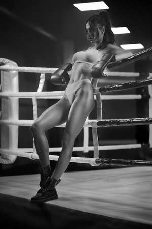 Full length portrait of brunette woman wearing boxing gloves, underwear and boots leaning on rope. Young female fighter posing in empty gym, black and white. Concept of sport, boxing. Standard-Bild
