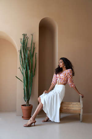 Gorgeous mulatto girl with long black curly hair posing near tall succulent plant, sitting on wooden wheel. Stunning half african young woman wearing blouse with floral print, white skirt and heels.