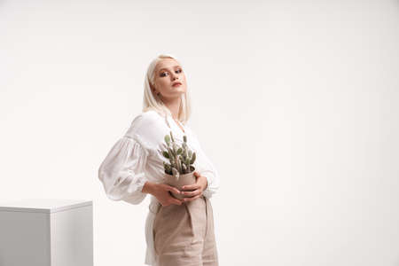 Isolated portrait of pretty girl wearing stylish blouse posing near box isolated on white studio background. Young blonde female model holding cactus in flower pot and looking at camera.