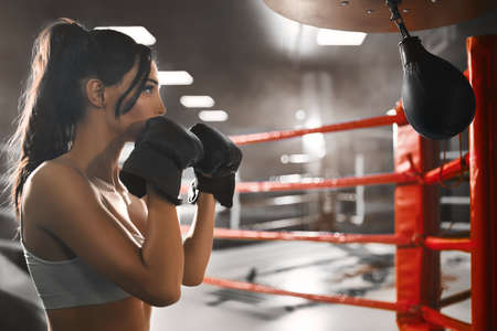 Side view of fit sexy concentrated brunette woman wearing boxing gloves. Young attractive fighter in beige top posing and hitting small punching bag on boxing ring. Concept of sport, boxing.