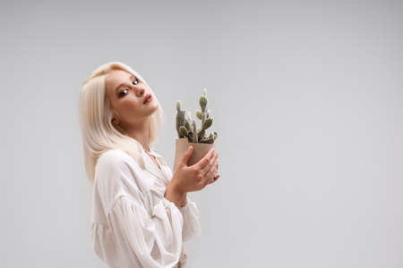 Side view of young blonde female model holding cactus in flower pot and looking at camera. Isolated portrait of pretty girl wearing stylish blouse posing isolated on gray studio background.