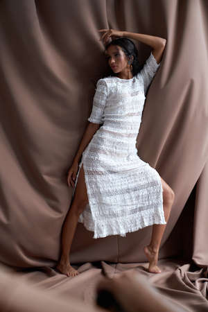Stunning barefoot half african brunette with perfect make up wearing white dress looking aside. Full length portrait of pretty mulatto girl with black curly hair posing among brown fabric indoors. Standard-Bild