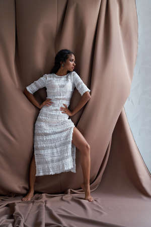 Full length view of pretty mulatto girl with black curly hair posing among brown fabric, hands on waist. Stunning barefoot half african brunette with perfect make up wearing white dress looking aside.