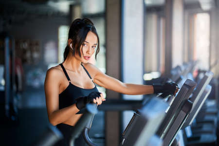 Side view of brunette woman in sportswear and wireless headphones doing cardio workout on orbitrek and looking at camera. Sexy muscular female with slim body running in empty gym. Concept of sport.