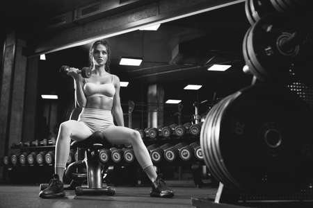 From below view of female bodybuilder training with dumbbells. Monochrome portrait of brunette fitnesswoman with fit body looking away, sitting on bench in gym. Concept of bodybuilding.