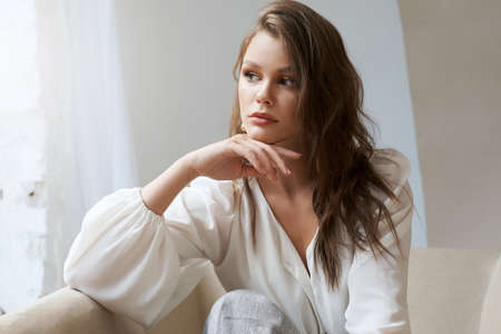 Portrait of stylish young pretty woman wearing fasionable white shirt posing indoors, sitting on light sofa. Front view of stunning girl with perfect nude make up and chestnut wavy hair looking aside.