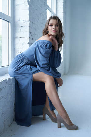 Side view of young girl with wavy hair posing on windowsill in room with white brick walls. Gorgeous female model wearing blue midi dress with wide neckline, heels and earrings, looking at camera.