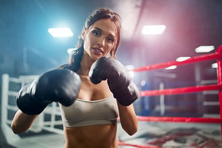 Front view of fit smiling brunette woman wearing boxing gloves. Young attractive fighter with perfect make up posing, looking at camera and showing hit on boxing ring. Concept of sport, boxing.