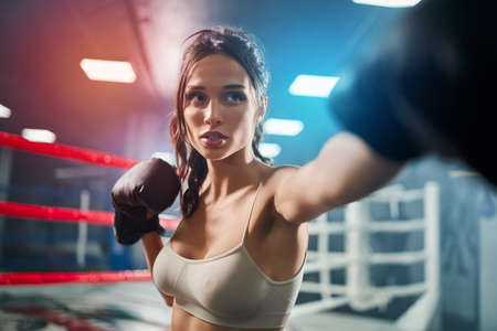Close up of fit concentrated brunette woman wearing boxing gloves. Young attractive fighter with perfect make up posing and showing hit on boxing ring, colorful lights on background.