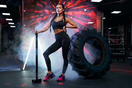 Side view of muscular woman in sportswear holding sledgehammer near tire wheel, looking at camera. Portrait of female bodybuilder posing in gym, having rest after hard training, red lights and smoke.