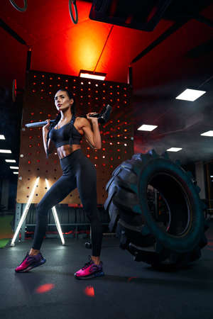Side view of muscular woman in sportswear holding sledgehammer on shoulders near tire wheel. Full length portrait of fit female bodybuilder posing in gym, having rest after hard training, red lights.