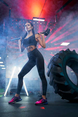 From below view of muscular woman in sportswear holding sledgehammer on shoulders near tire wheel, smoky atmosphere. Portrait of fit female bodybuilder posing in gym, having rest after hard training. Imagens