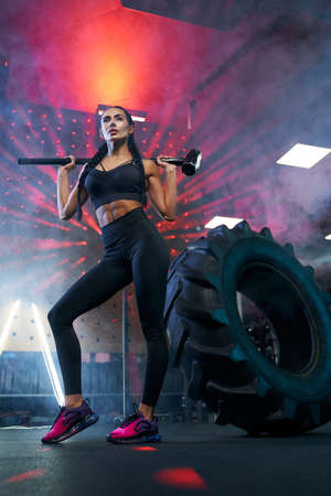 From below view of muscular woman in sportswear holding sledgehammer on shoulders near tire wheel, smoky atmosphere. Portrait of fit female bodybuilder posing in gym, having rest after hard training.