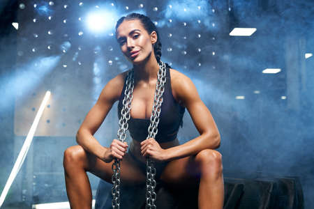 Young smiling fitness woman in black sportswear with braids holding chains on neck. Front view of athlete female with perfect body sitting in gym, looking at camera. Concept of sport, bodybuilding. 写真素材