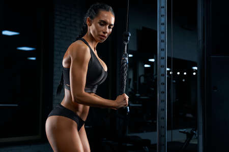 Side view of woman in sportswear with long braids and perfect buttocks training triceps. Attractive female with strong body building muscles with crossover. Concept of sport, bodybuilding.