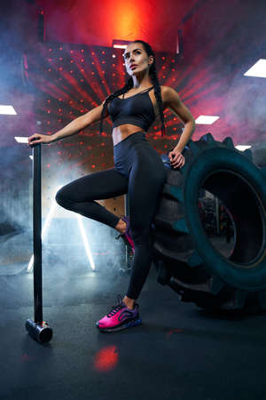 From below view of fit woman in sportswear holding sledgehammer, looking up. Portrait of female bodybuilder posing in gym, having rest after hard training near tire wheel, red lights and smoke.