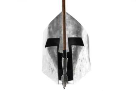 Selective focus of sharp wooden arrow, medieval iron silver helmet on background. Old ancient armour and weapon isolated on white, nobody.