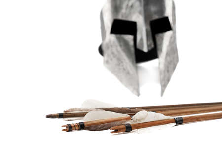 Close up cropped view of ancient metal silver helmet and wooden arrows with grey feathers isolated on white background. Medieval armour and old defensive weapon.