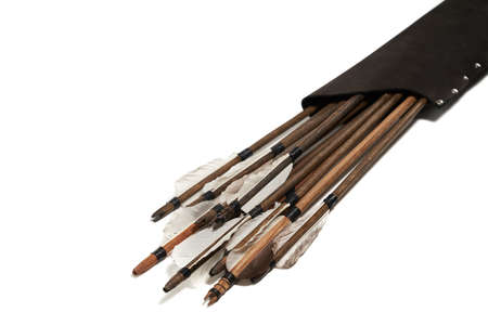 Closeup view of ancient wooden arrows with grey feathers isolated on white background. Qualitative old medieval weapon in black leather case.