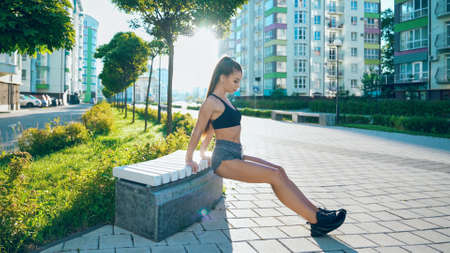 Side view of young charming muscular woman practicing back triceps dips using bench outdoors. Fit attractive girl with perfect body training near multistorey buildings in sunny summer morning.