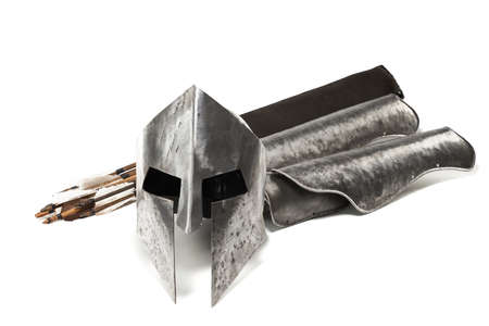 Close up view of medieval iron armour and weapon isolated on white. Crop of ancient metal silver helmet, hand protecction and wooden arrows in black bag on background.