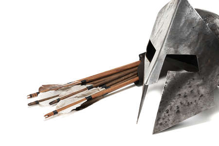 Close up side view of medieval armour and weapon. Crop of ancient metal silver helmet and wooden arrows isolated on white background.