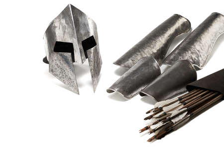 Close up view of medieval iron armour and weapon. Crop of ancient metal silver helmet, hand protecction and wooden arrows in black bag isolated on white background. Reklamní fotografie