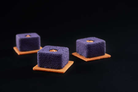 Purple matte purple dessert filled with brown creme isolated on black studio background. Closeup view of three small square matte cakes on cookies in restaurant. Concept of confectionary.