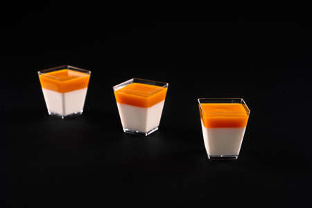 Sweet dessert decorated with bright orange topping, isolated on black studio background. Front view of three small square glasses with delicious milky panna cotta. Food concept.