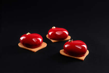 Red heart cakes decorated with gold isolated on black background. Dessert with smooth surface, mousse and mirror glaze on sweet cookies. Delicious dish in cafeteria.