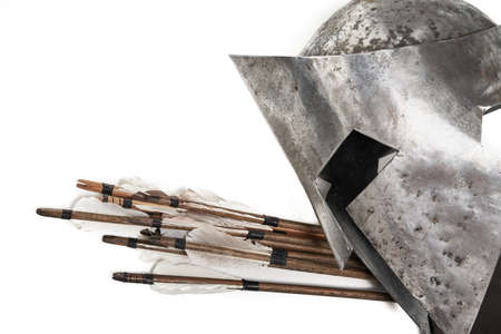 Close up side view of ancient iron silver helmet and wooden arrows with feathers. Medieval armour and weapon isolated on white background.