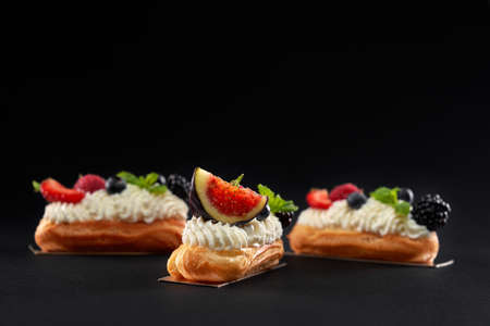 Front view of fresh dessert in row isolated on black background. Baked homemade eclairs filled with cream, white topping and slices of figs, blackberries, raspberries and blueberries.