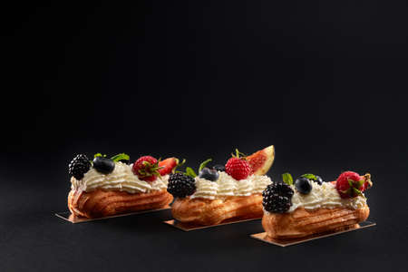 Baked homemade eclairs filled with cream, white topping and slices of figs, blackberries, raspberries and blueberries. Side closeup view of fresh dessert in row isolated on black background.