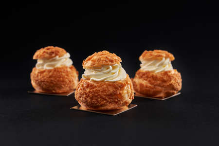 Closeup view of hree delicious fresh profiteroles with sweet white cream inside. Homemade tasty eclairs isolated on black studio background. Concept of desserts, restaurant food. Reklamní fotografie