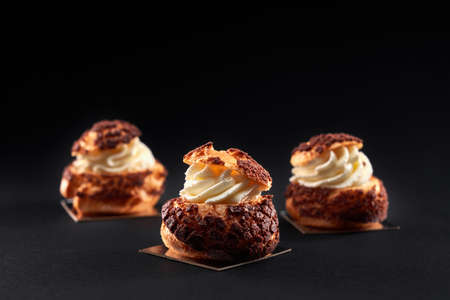 Three delicious fresh crunchy profiterole balls in row with sweet white cream inside. Closeup of homemade tasty brown eclairs isolated on black background. Concept of desserts, restaurant food.