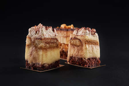 Closeup view of three square pieces in row decorated with whipped cream and cocoa, isolated on black. Tiramisu cake with three layers of chocolate biscuit and coffee syrup with cognac and cream.