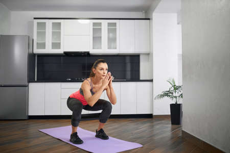 Strong caucasian young woman squatting on mat in kitchen. Fit girl wearing sportswear training at home in morning using resistance band. Concept of home workout, weight loss. Reklamní fotografie
