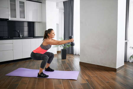 Side view of fit caucasian young woman squatting in kitchen and smiling in morning. Strong girl wearing sportswear training legs on mat at home carrying dumbbell in hands. Concept of home workout.