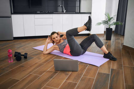 Side view of strong young woman practicing crunches in kitchen, watching video on laptop. Fit girl wearing sports clothes training abs on mat at home in morning. Concept of home workout.