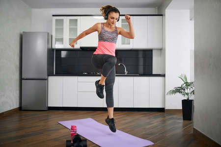 Side view of strong young woman jumping on mat in kitchen. Fit girl wearing sports outfit and headphones training at home in morning, listening to music. Concept of home cardio workout, weight loss. Reklamní fotografie