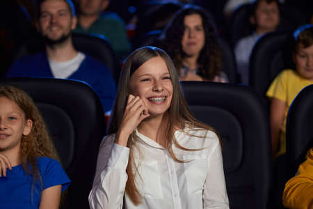 Portrait of young girl watching movie in cinema, laughing with teeth, dental braces. Cheerful caucasian female teenager wearing white shirt enjoying film with friends. Entertainment concept.