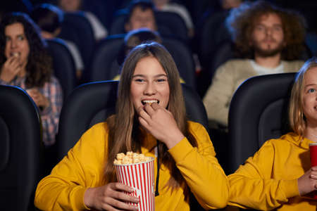 Selective focus of young girl watching movie in cinema, eating popcorn and laughing. Cheerful caucasian female teenager wearing yellow sweater enjoying film with friends. Entertainment concept.