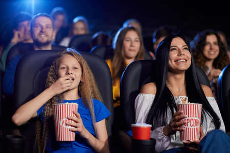 Portrait of stunning brunette girl watching movie with younger sister in cinema, laughing with teeth. Cheerful caucasian female teenager wearing shirt, eating popcorn, enjoying film with family.