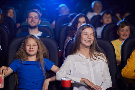 Portrait of girl watching movie with younger sister in cinema, laughing with teeth, dental braces. Cheerful caucasian female teenager wearing shirt enjoying film with family. Entertainment concept.