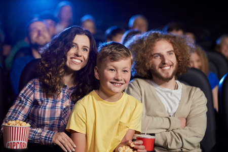 Selective focus of young parents with curly hair enjoying time with son holding sparkling drink, audience on background. Happy family sitting in cinema, kid on knees, watching funny cartoon.